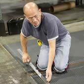 Man measuring and cutting matting
